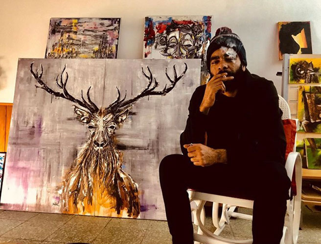 Portrait of artist Nitael with various new works in his studio
