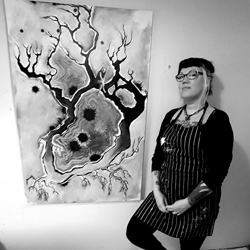 Portrait of Canadian born artist Shannon Rakochy beside one of her new paintings